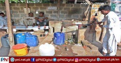Residents of Korangi area filling canes through water hand pump